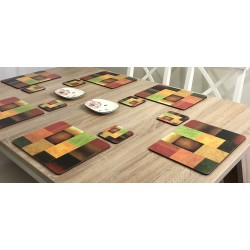 Angled view of Plymouth Pottery Majestic design of vibrantly coloured corkbacked placemats on wooden dining table